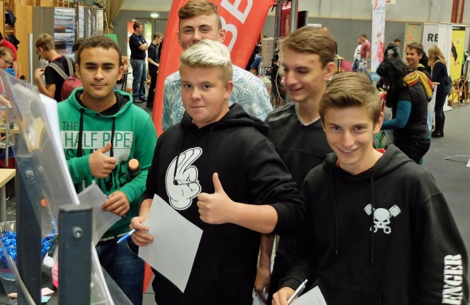 """Das Bild zeigt eine Gruppe Jugendlicher beim Besuch eines Messestandes in der Position """"Daumen hoch""""."""