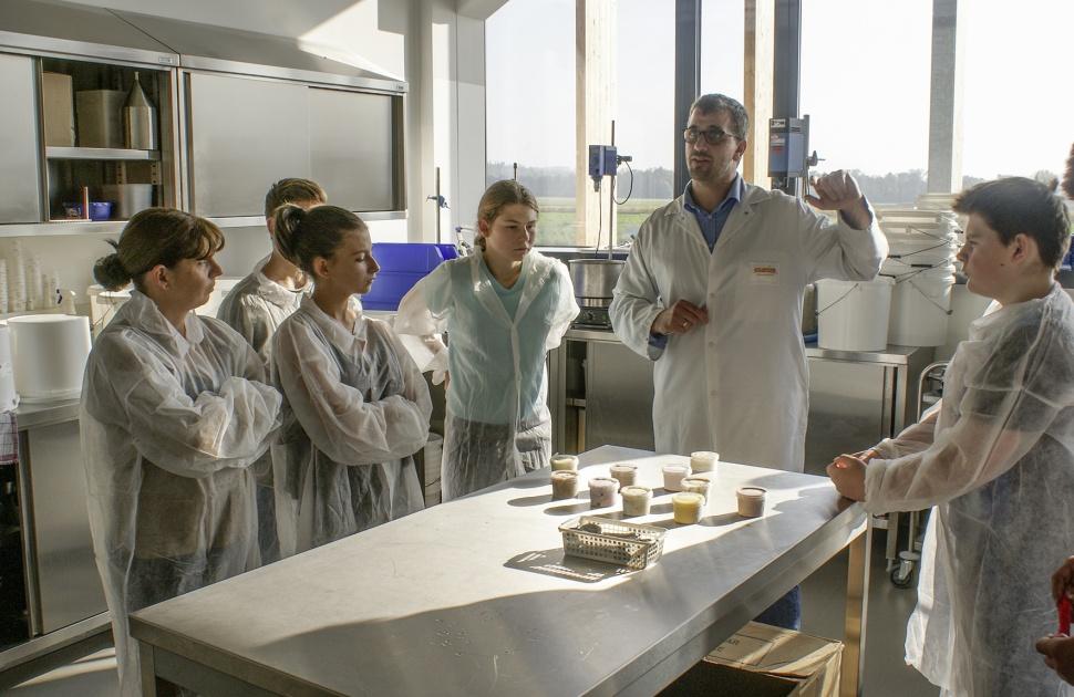 Ein Mitarbeiter eines Lebensmittelbetriebs erklärt Schülerinnen und Schülern in Schutzkleidung einen Arbeitsprozess.