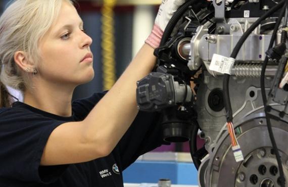 Eine junge Frau serviciert einen Motor.